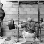Dave Draper instructs Arnold Schwarzenegger on squatting.
