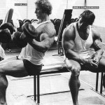 Ken Waller does biceps work aka dumbbell curls as Arnold Schwarzenegger looks onward