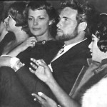 Women are distracting Steve Reeves from watching himself on screen.
