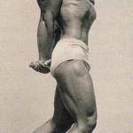 Steve Reeves displays triceps development at beach.