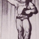 Steve Reeves hits a biceps shot while holding trophy.